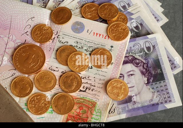 British passport with Saudi Arabian visa together with gold and cash - Stock Image