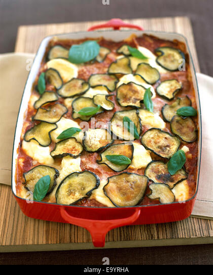 baked lasagna in red pan with eggplant slices and basil leaves - Stock Image