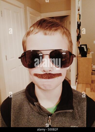 Kid with fake mustache and glasses - Stock Image