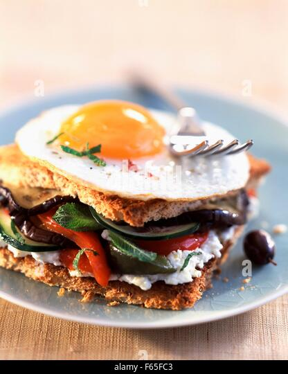 Toasted sandwich with fried egg, vegetables and goat's cheese - Stock Image