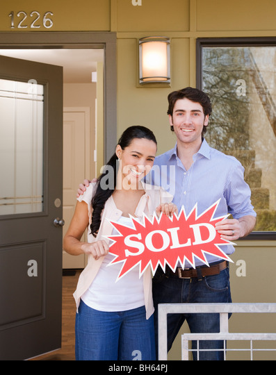 couple on front porch with sold sign - Stock-Bilder