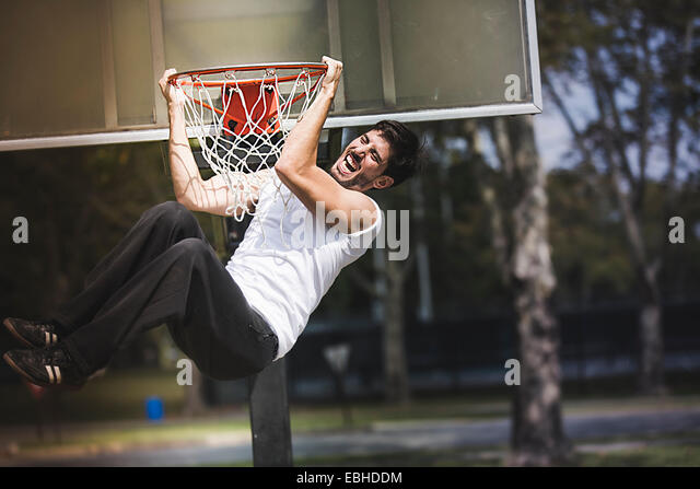 Young male basketball hanging from basketball hoop - Stock Image