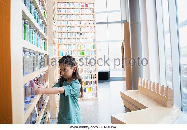 Girl touching jar on shelf science center - Stock Image