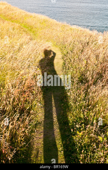 Long shadow of photographer in late afternoon light, Sherwink Trail, near Trinity East, Newfoundland, Canada - Stock Image