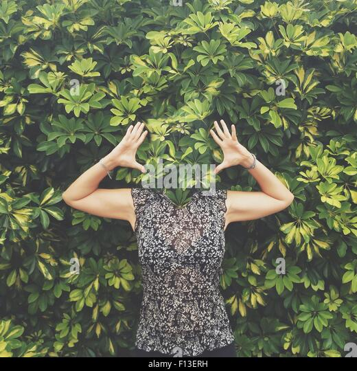 Women with face hidden behind leaves standing with raised arms - Stock Image