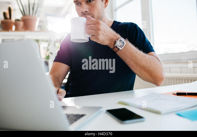 Businessman drinking coffee and working on laptop at workplace. Male executive working at his desk and drinking - Stock Image