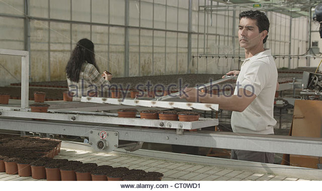 Worker with pots in factory - Stock Image