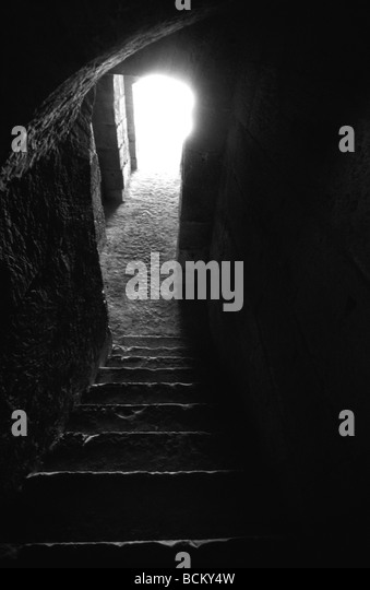 Dark staircase with light coming from doorway, black and white - Stock-Bilder