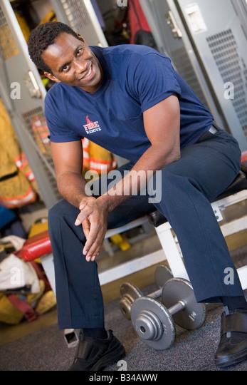 Fireman sitting on bench in fire station locker room - Stock Image