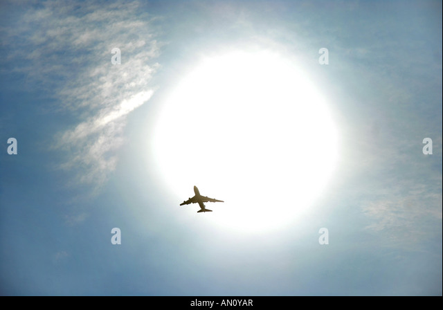 commercial jet aircraft flying in front of the sun. - Stock Image