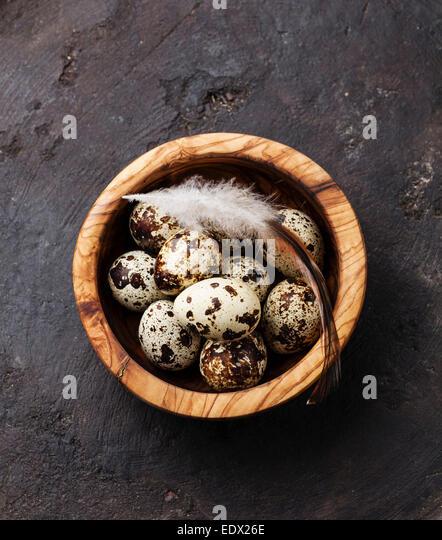Olive wood bowl with fresh quail eggs on dark background - Stock Image