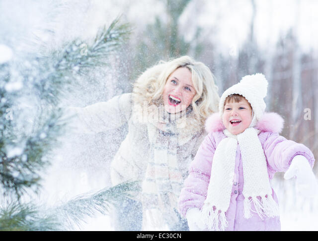 Happy mopther and kid playing with snow in winter outdoor - Stock Image