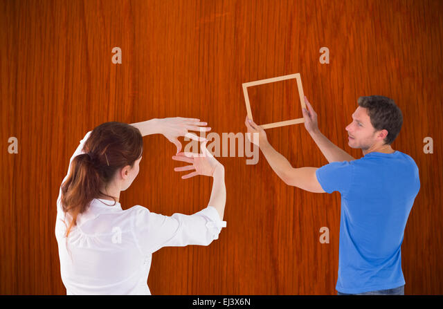 Composite image of couple deciding to hang picture - Stock Image