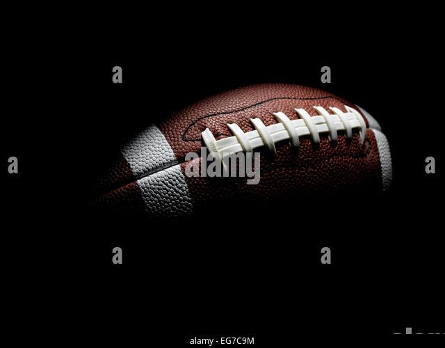 Flying Football on Black - Stock Image