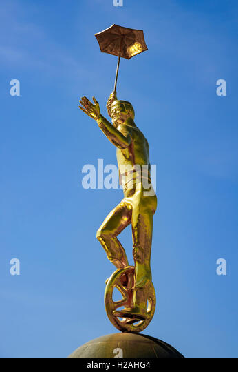 Golden Acrobat statue (clown) riding a bike at Moscow Fountain Circus square, Astana, Kazakhstan - Stock Image