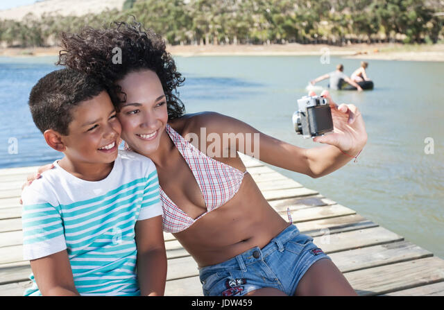 Woman taking self portrait photo with boy sitting on jetty - Stock-Bilder