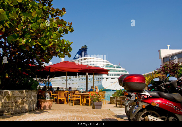 st george bermuda coupe dining at oudoor cafe with red umbrellas and cruise ship in backgroud red moped - Stock Image