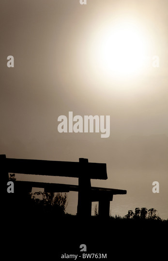 Empty bench looking across a misty expanse - Stock Image