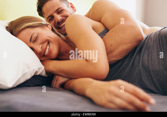 Image of cute young couple in love lying on bed. Man waking up his wife in morning. - Stock Image