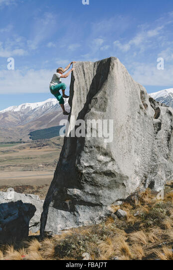 New Zealand, Castle Hill, Young man climbing up steep rockface - Stock Image