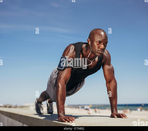 Muscular man doing push ups against blue sky. Strong male athlete working out outdoors. - Stock-Bilder