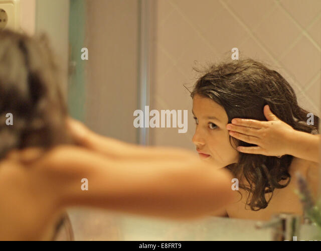 Girl with wet hair looking at reflection in mirror - Stock Image