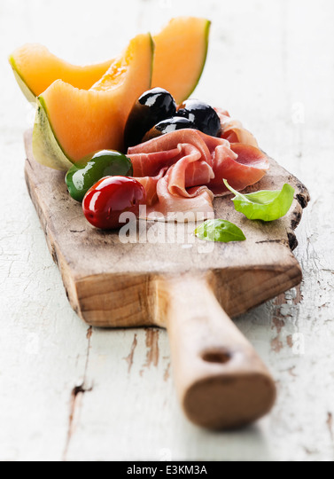 Prosciutto ham, Slices of melon cantaloupe and Olives on cutting board - Stock Image