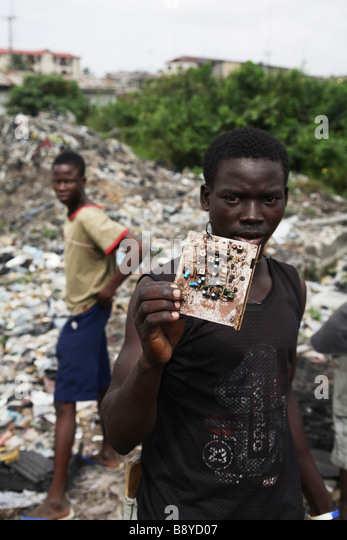 Electronic waste in Lagos, Nigeria. A boy is showing electronic waste, a circuit board, which can be found on the - Stock Image