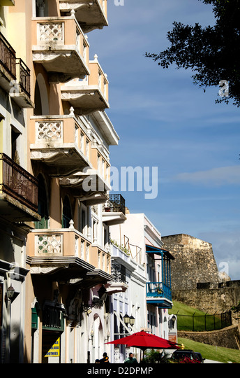 Colorful apartment buildings in Old San Juan with Castillo San Cristóbal fort in background, Puerto Rico - Stock Image