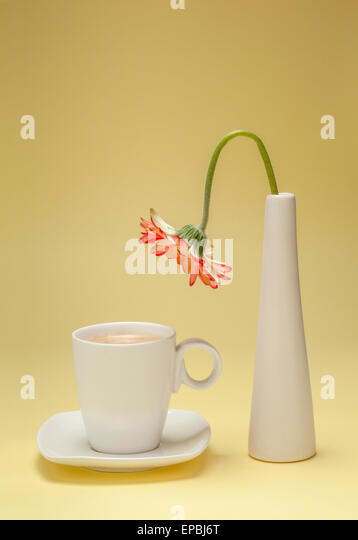 Thirsty flower bending over a cup of coffee - Stock Image