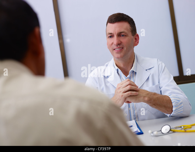 Friendly doctor working and giving assistance to old male patient in hospital office. Focus on background - Stock Image