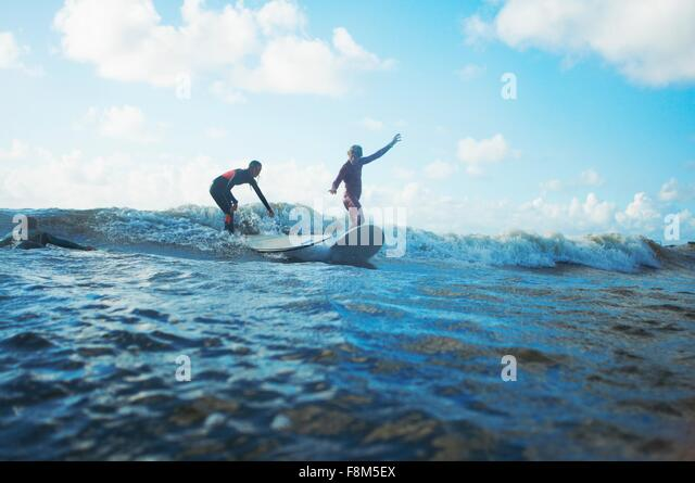 Two surfers surfing in sea - Stock Image