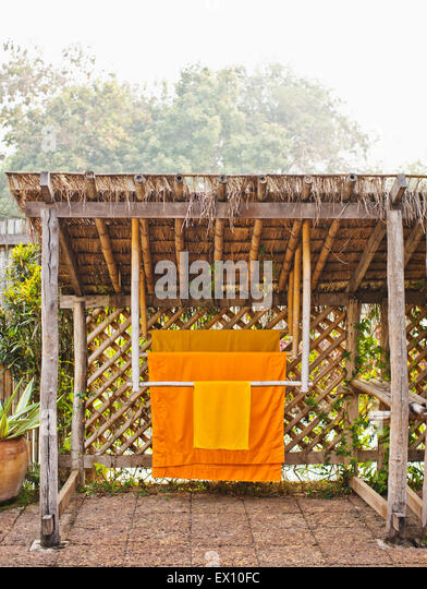 Monk robes hang in the private garden of Room #506, La Residence Phou Vao. Luang Prabang, Laos. - Stock Image