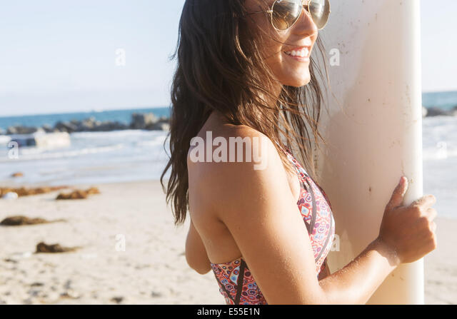 Young female surfer with sunglasses smiling while holding surfboard at the beach - Stock Image