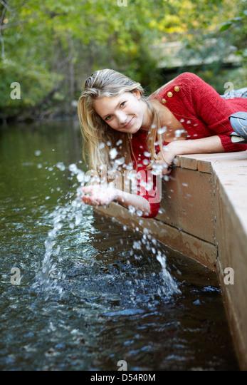 Teen girl splashing water on dock - Stock Image