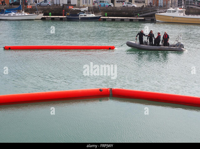 Oil pollution containment boom deployment exercise at Weymouth Harbour, Dorset, UK - Stock Image