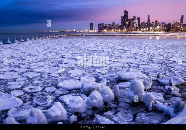 USA, Illinois, Chicago, Illuminated skyline seen across icy harbor - Stock Image