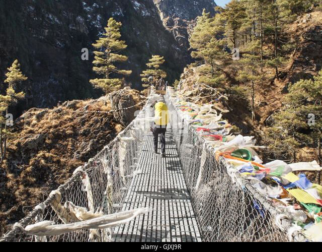 A hiker crosses a suspended bridge in Nepal's Everest Base Camp - Stock Image