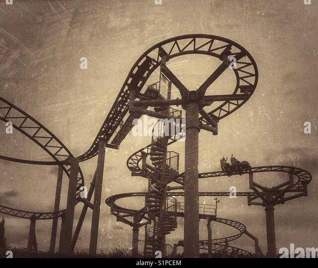 A distressed & antique effect image of children riding on a rollercoaster ride in an amusement park. Photo Credit - Stock Image