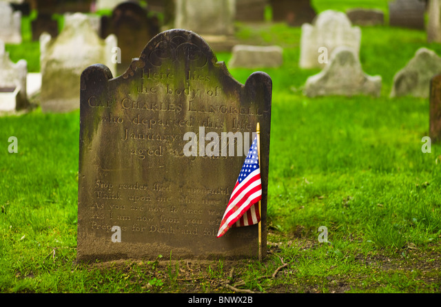 American flag in front of tombstone - Stock Image