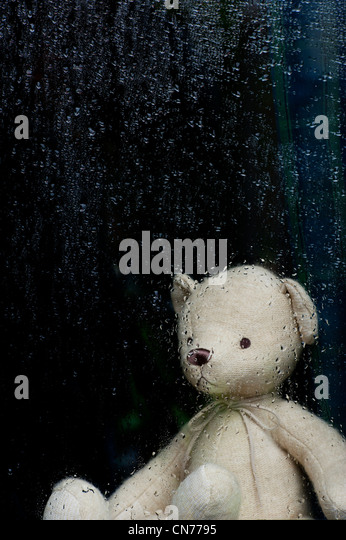 Sad Teddy bear looking through a window covered in rain drops - Stock Image