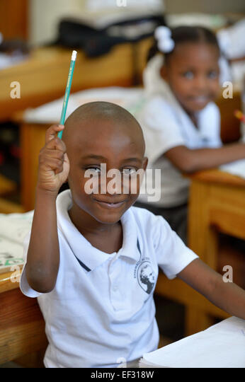 Schoolboy raising his hand in class, class at the Basile Moreau Primary School, Carrefour, Port-au-Prince, Ouest - Stock Image