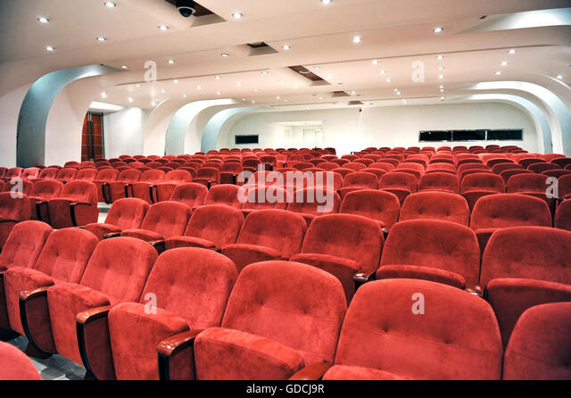 Rows of empty red seats for spectators in an auditorium, cinema or entertainment venue viewed close up - Stock Image