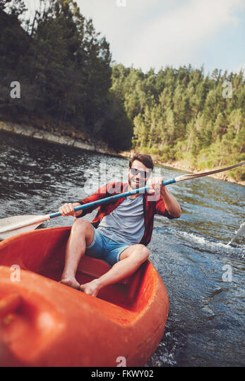 Portrait of smiling young man paddling kayak in a lake. Young guy canoeing on a lake. - Stock Image