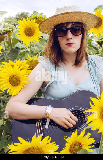 Young country woman with her black guitar - Stock Image