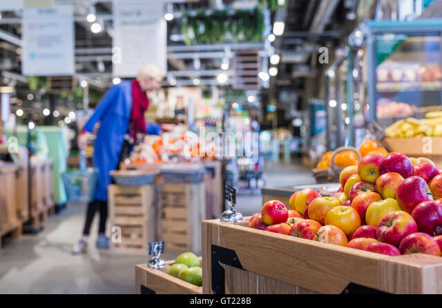 Apples in wooden crates with woman shopping at supermarket - Stock-Bilder