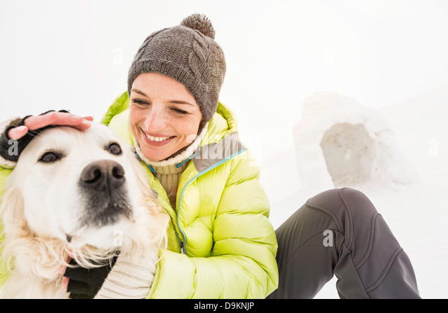 Woman in knit hat patting dog's head - Stock Image