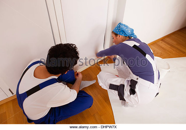 Decorating wallpaper young couple new home moving - Stock Image