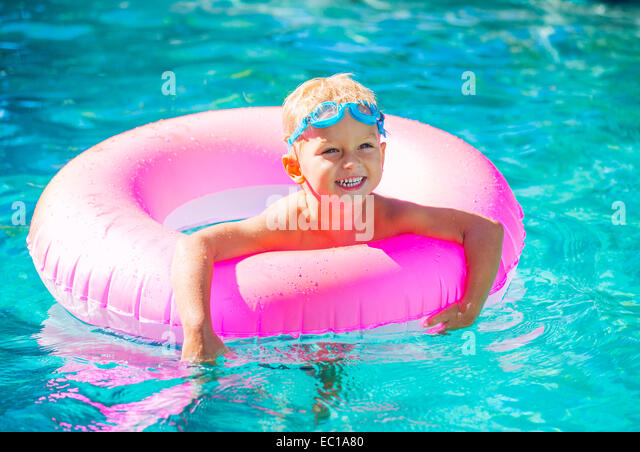 Little Kid Having Fun in Swimming Pool, with Goggles and Raft. Summer Vacation Fun. - Stock Image