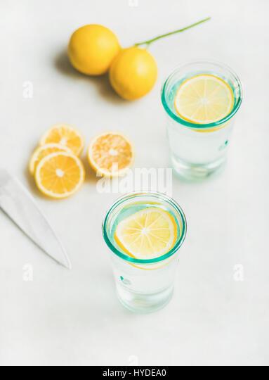 Detox lemon water in glasses served with fresh lemon fruits - Stock Image